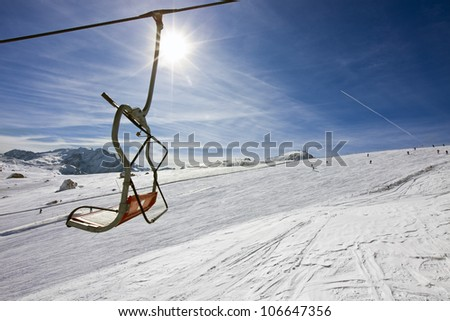 vacant chair of a ski-lift above a ski slope