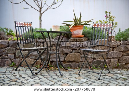 Vacant wrought iron table and chairs on an outdoor patio standing on paving alongside a walled rock garden with a potted cactus on the wall - stock photo