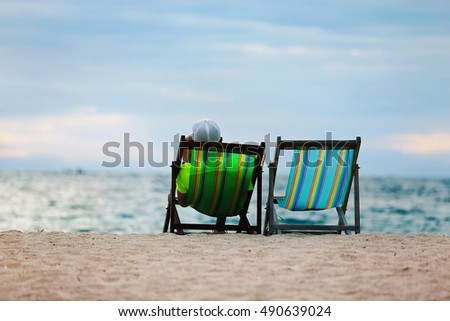 vacation at the beach, a man wearing a white cap watching the sea view on the beach chair