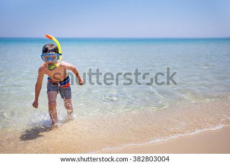 Vacation boy happy snorkeling running having fun in water splashing during summer holiday vacation - stock photo