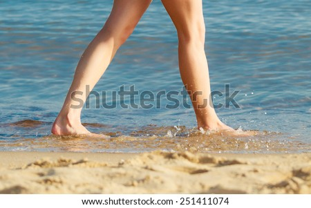 Vacation. Closeup of female feet. Woman walking alone on the empty beach. Young woman relaxing on the sea coast. Summertime. - stock photo
