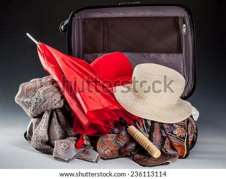 Vacation composition: red umbrella, summer hat and silk kerchiefs in opened suitcase - stock photo