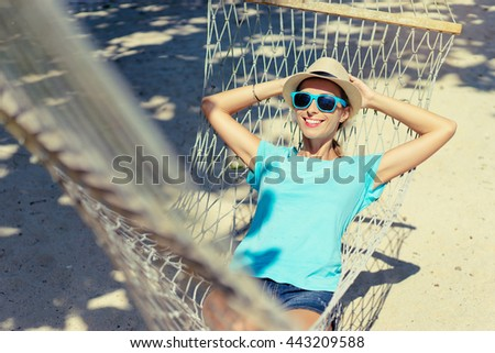 Vacation concept. Enjoying the summer. Young pretty woman in hat and sunglasses laying in hammock on the beach.