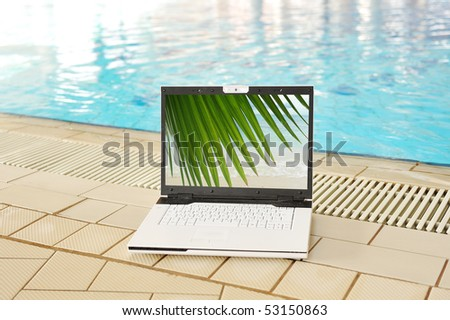 Vacation concept, laptop on pool - stock photo