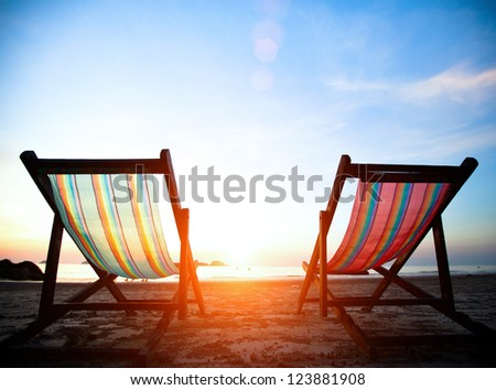 Vacation concept: Pair of beach loungers on the deserted coast sea at sunrise. - stock photo