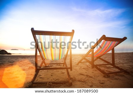 Vacation concept, pair of beach loungers on the deserted coast sea at sunrise. - stock photo