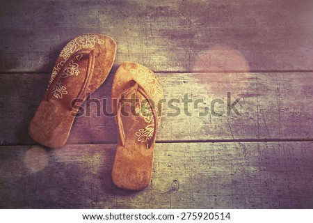 Vacation Concept. Pair of beach sandals on wood background - stock photo