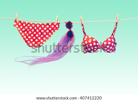Vacation concept. Summer Beach clothes and accessories stylish set. Fashion swimsuit bikini red polka dots, sunglasses on rope. Essentials creative tropical look on blue. Ocean sea, vintage - stock photo