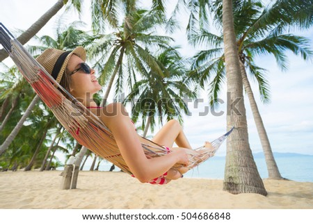 Vacation concept. Young pretty woman in hat and sunglasses laying in hammock on the beach. Selective focus.