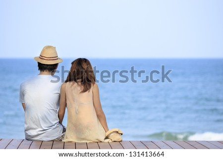 Vacation couple on beach together in love holding around each other - stock photo