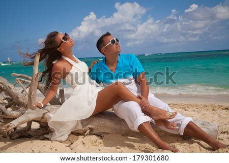 Vacation couple relaxing on tropical beach together in love. Honeymoon in Dominican Republic.