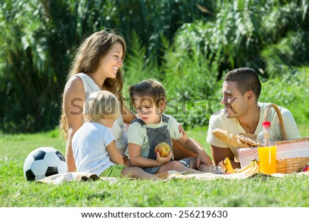 Vacation day of happy young family with picnic at countryside