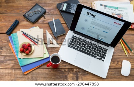 Vacation entertainment concept.  Handcrafted countryside style wooden desk items in creative disorder laptop computer internet page on screen color pencils booklets plate strawberry coffee mug - stock photo