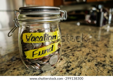 "Vacation Fund Money Jar. A clear glass jar filed with coins and bills, saving money. The words ""Vacation Fund"" written on the outside. - stock photo"