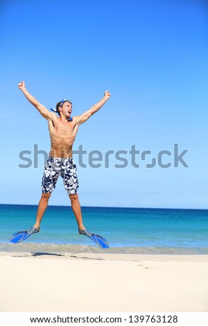 Vacation - happy beach man jumping with snorkeling fins and mash excited about summer holidays travel on tropical beach. Fit male model in swimwear with snorkel going swimming in blue sea. - stock photo