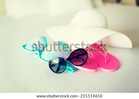 vacation, holiday and travel concept - close-up of bikini top, straw hat, flip-flop and sunglasses on hotel bed