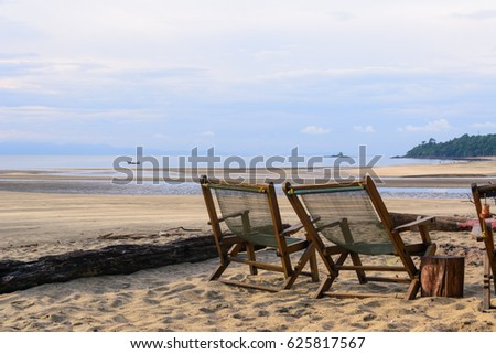 Vacation holidays background wallpaper - two beach lounge chairs under tent on beach.