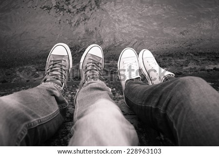 Vacation holidays. Close up of girl's and boy's feet relaxing by the river