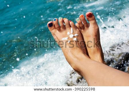 Vacation holidays. Woman feet close up of girl on beach enjoying sun. Rainbow manicure, sun of sunscreen - stock photo