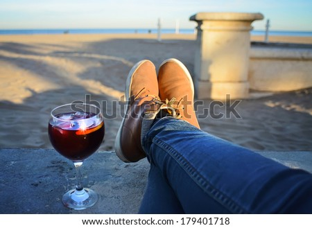 Vacation holidays. Woman feet closeup of girl relaxing on beach on sunbed enjoying sun on sunny spring day,glass of sangria - stock photo