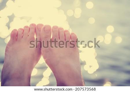 Vacation holidays. Woman feet closeup of girl relaxing on beach on sunbed enjoying sun on sunny summer day. - stock photo