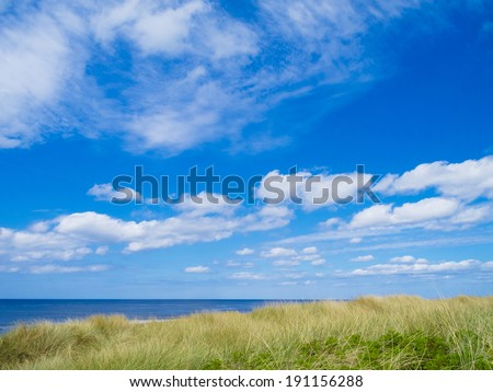 vacation image with dunes, blue sea and beautiful sky - stock photo