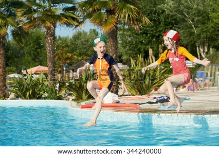 Vacation. little fun children girl and boy jumping into swimming pool - stock photo