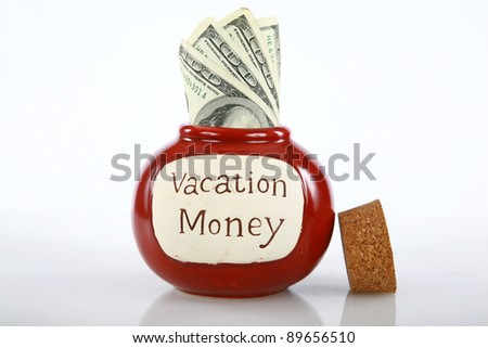vacation money jar jam packed with cash isolated on white with room for your text - stock photo