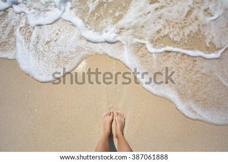 Vacation on ocean beach, feet on sea sand - stock photo