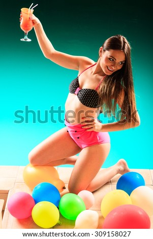 Vacation party and fun cocncept. Beauty woman with tropical drink in hand on pool with balloons.