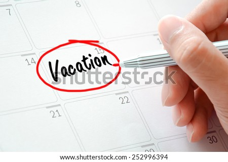 Vacation text on the calendar (or desk planner) circled with red marker - stock photo