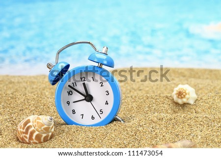 Vacation time. Alarm clock on the sand - stock photo