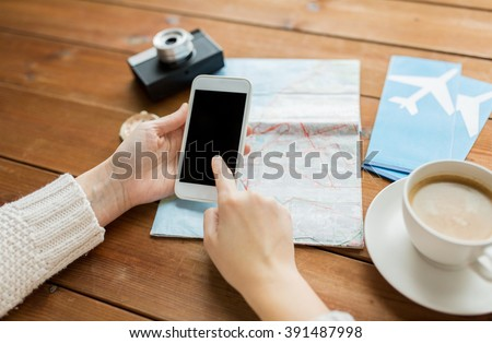 vacation, tourism, travel, technology and people concept - close up of traveler hands with blank smartphone screen and map - stock photo