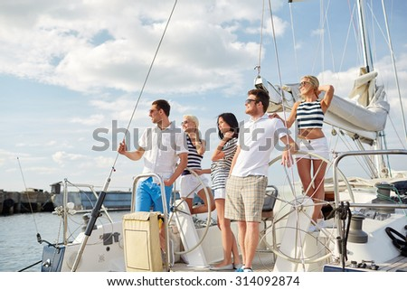 vacation, travel, sea, friendship and people concept - smiling friends sailing on yacht - stock photo