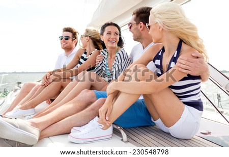 vacation, travel, sea, friendship and people concept - smiling friends sitting on yacht deck - stock photo