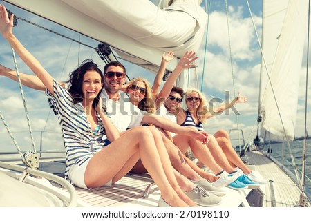 vacation, travel, sea, friendship and people concept - smiling friends sitting on yacht deck and greeting - stock photo