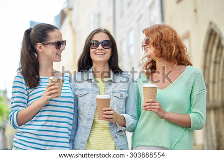 vacation, weekend, takeaway drinks, leisure and friendship concept - smiling happy young women or teenage girls drinking coffee from disposable paper cups on city street