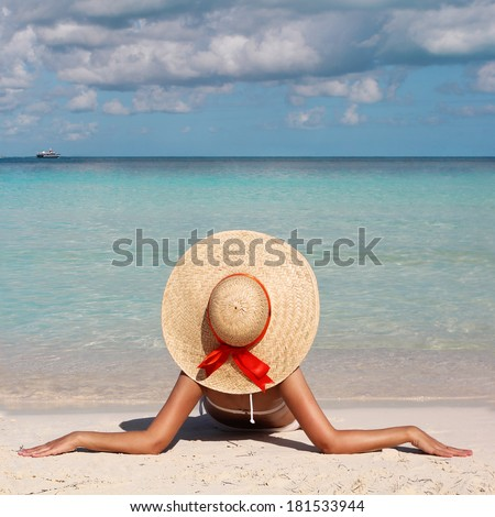 Vacation. Woman in Big Sun Hat tanning and relaxing on Tropical Beach.  - stock photo