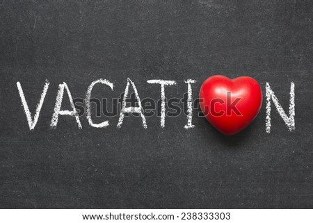 vacation word handwritten on chalkboard with heart symbol instead of O