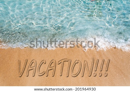 Vacation word sign on the beach sand  - stock photo