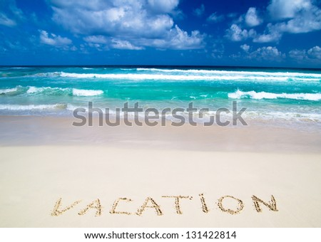 vacation written in a sandy tropical beach