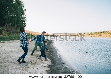 vacation young family near the lake, happy father, mother and son running on beach - stock photo