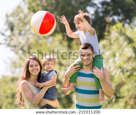 Vacation young family of four in the park summer day - stock photo