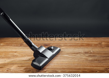 vacuum cleaner brush on wooden floor - stock photo