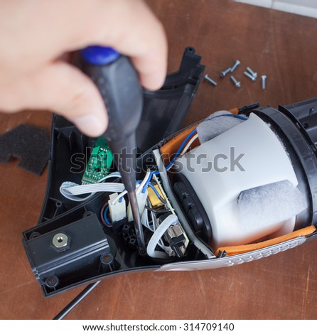 Vacuum cleaner disassembled for repair malfunctioning on work table - stock photo