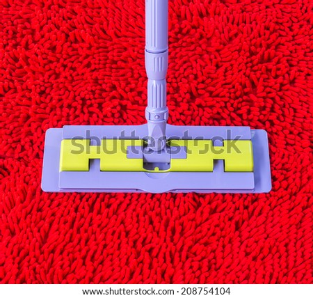 Vacuum cleaner for cleaning on red carpet - stock photo