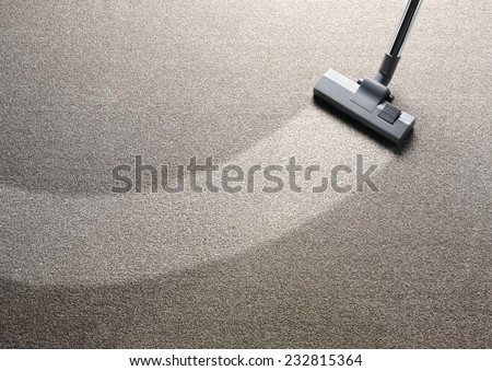 Vacuum cleaner on a carpet with an extra clean strip for copy space  - stock photo