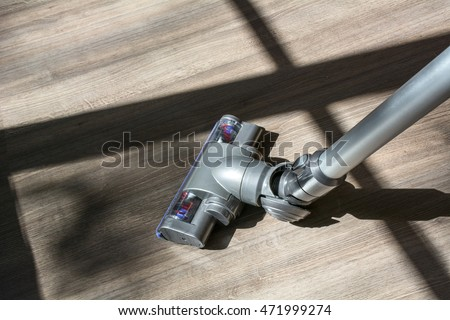 Vacuum cleaner on the brown wooden floor in the sunlight