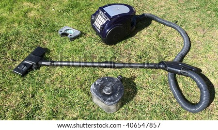 Vacuum cleaner stands on a spring grass. It's time to clean up your car.