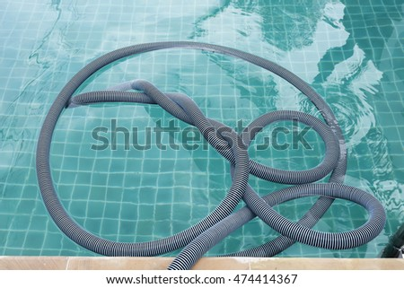 Vacuum hose on swimming pool water surface, outdoor day light